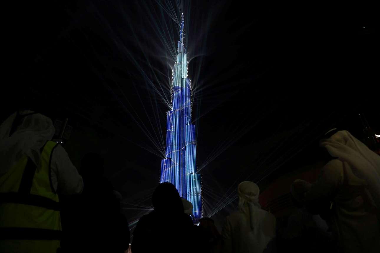 Κόσμος θαυμάζει τον ουρανοξύστη Μπουρτζ Χαλίφα, καθώς φωταγωγείται για να εορτάσει τον ερχομό του 2018, στο Ντουμπάι