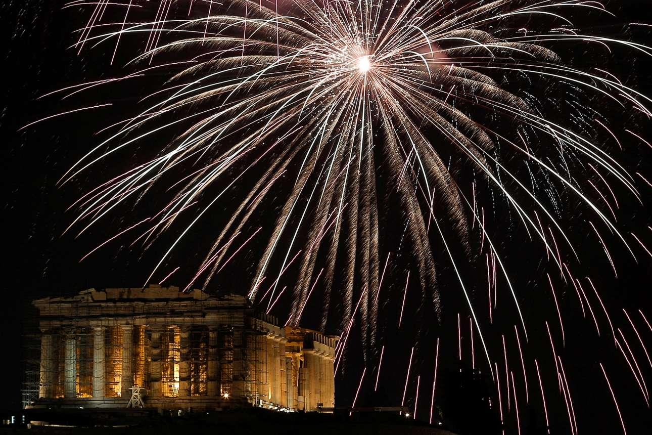 Αθήνα, ώρα 12 τα μεσάνυκτα. Ο ουρανός πάνω από τον Ιερό Βράχο της Ακρόπολης φωτίζεται από τα πυροτεχνήματα στις γιορτές του Δήμου Αθηναίων