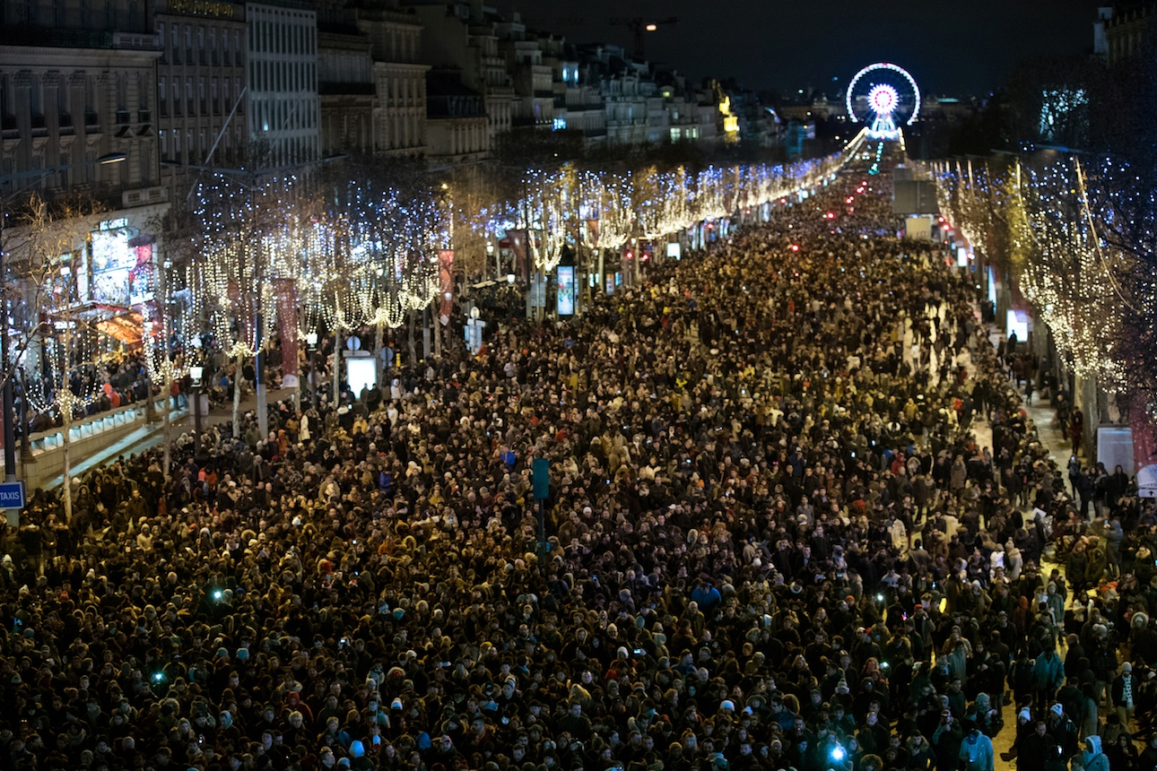 Πολύς κόσμος, αλλά όχι και τόσο πολύς ώστε να γεμίσει ασφυκτικά τον χώρο, γιορτάζει το 2018 στα Ηλύσια Πεδία, στο Παρίσι