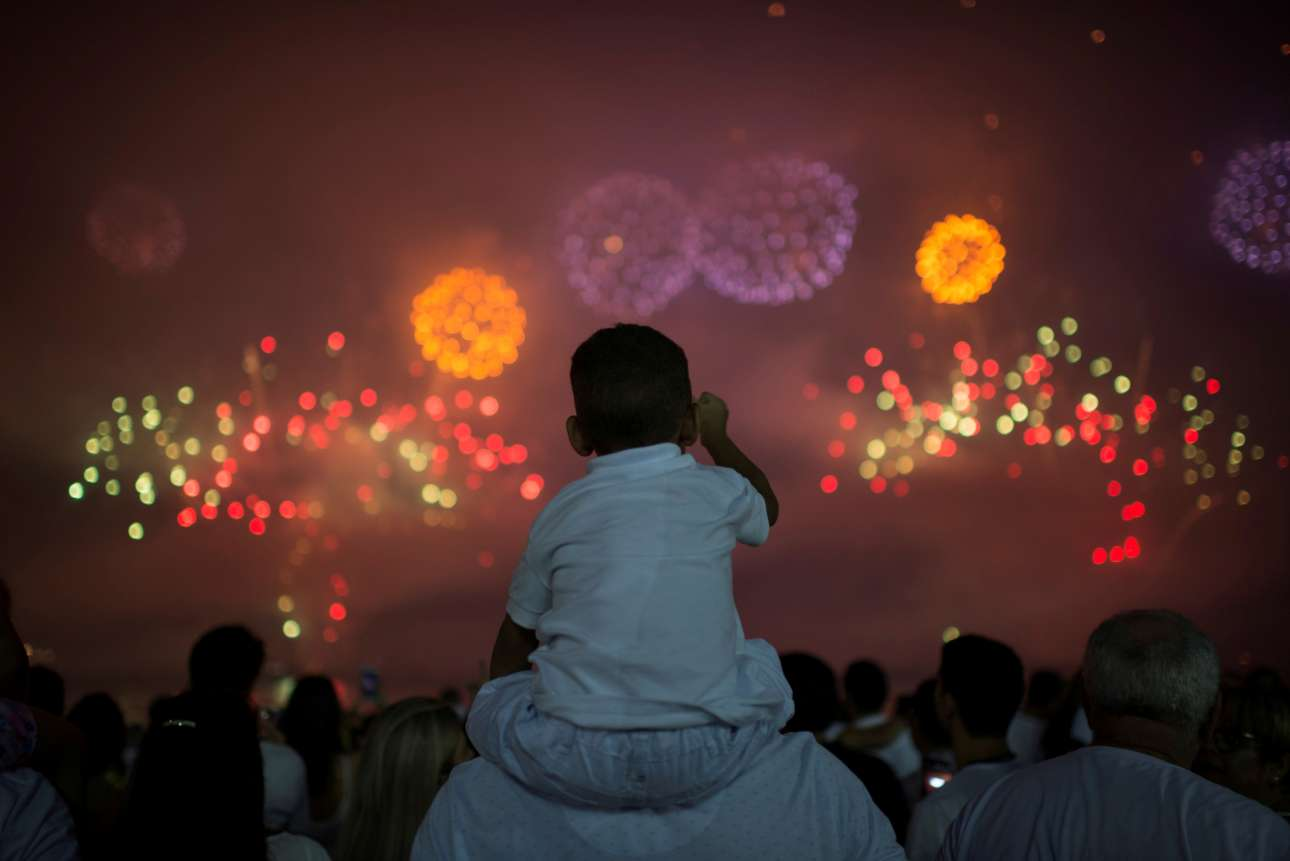 Μπαμπά, αυτό είναι το 2018; Ενας πιτσιρίκος δεν κοιμάται. Επάνω στις πλάτες του πατέρα του θαυμάζει τα πυροτεχνήματα στο Ρίο ντε Τζανέιρο