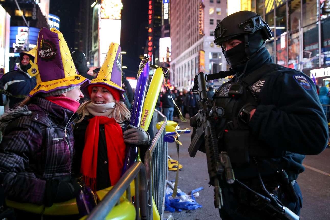 Πάνοπλος αστυνομικός συζητά με δυο κορίτσια στην Τάιμς Σκουεάρ εν αναμονή του νέου χρόνου