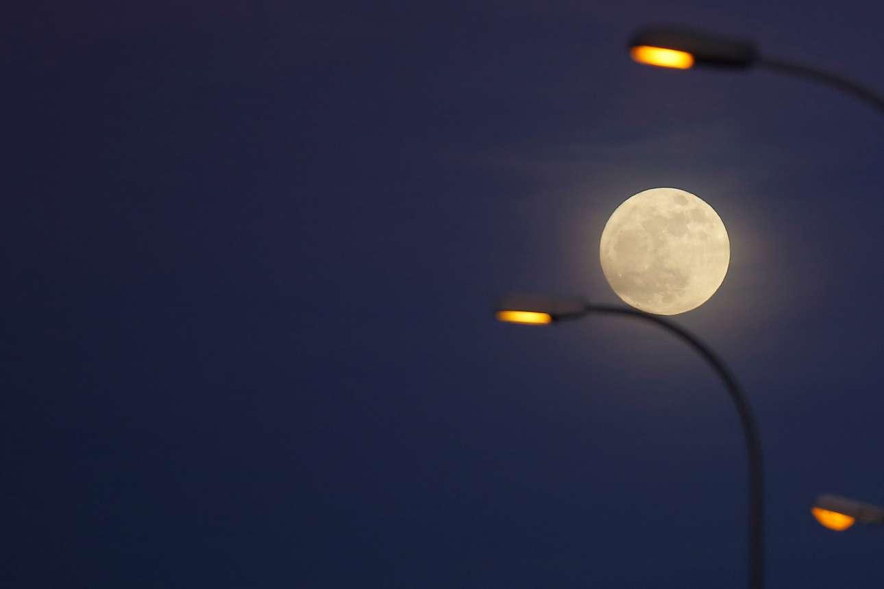 Η πανσέληνος ισορροπεί πάνω στα φανάρια του δρόμου στη Ρόντα της Ισπανίας