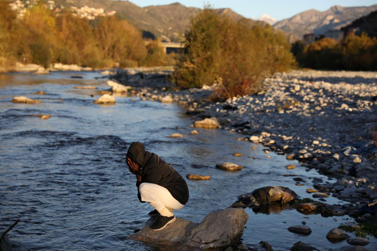 Ανδρας πλένει το πρόσωπό του σε ένα παγωμένο ποτάμι αφού πέρασε όλο το βράδυ κάτω από μία γέφυρα τρένων