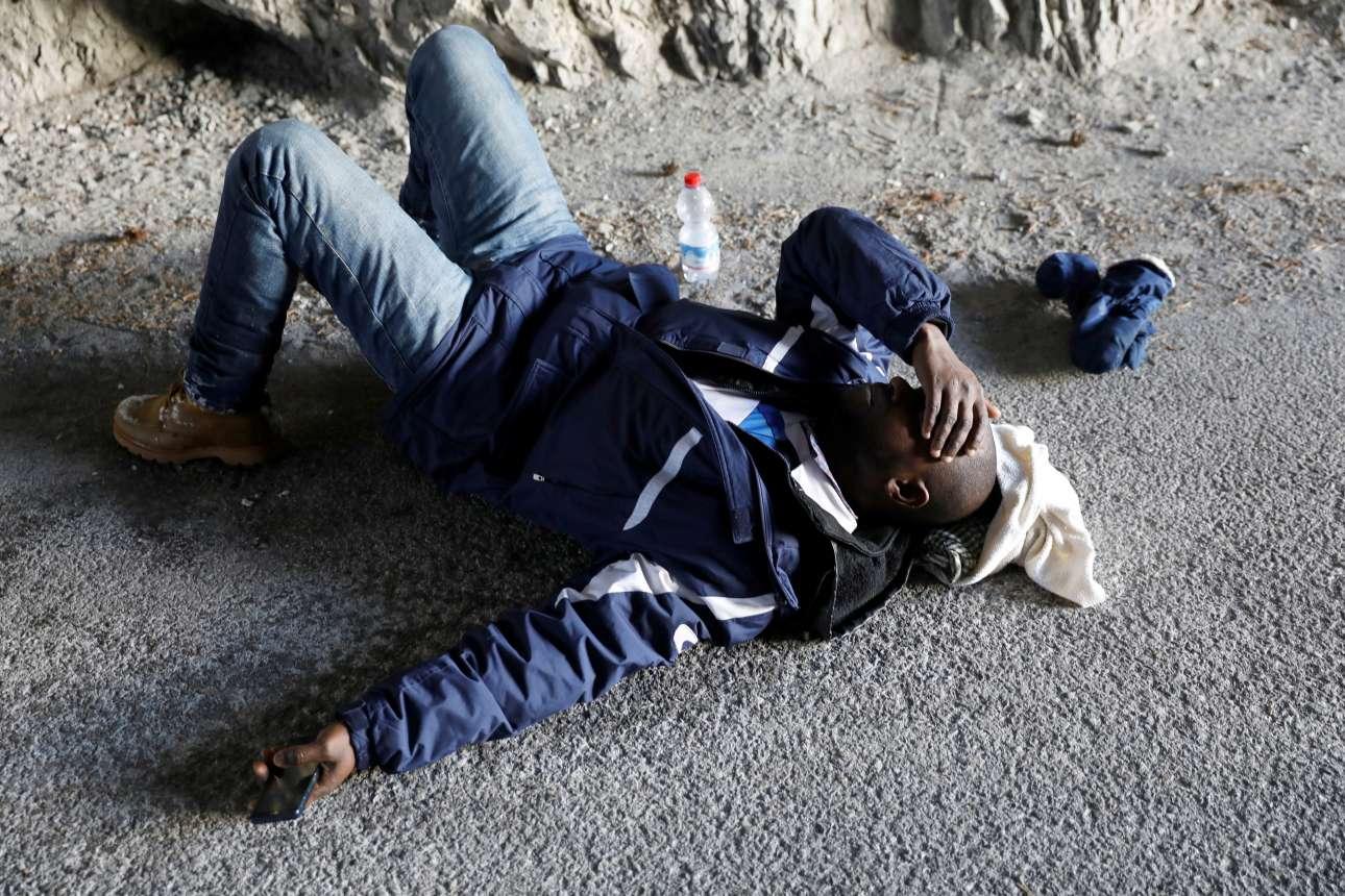 Εξουθενωμένος μετανάστης παίρνει μερικές ανάσες για να συνεχίσει το ταξίδι του