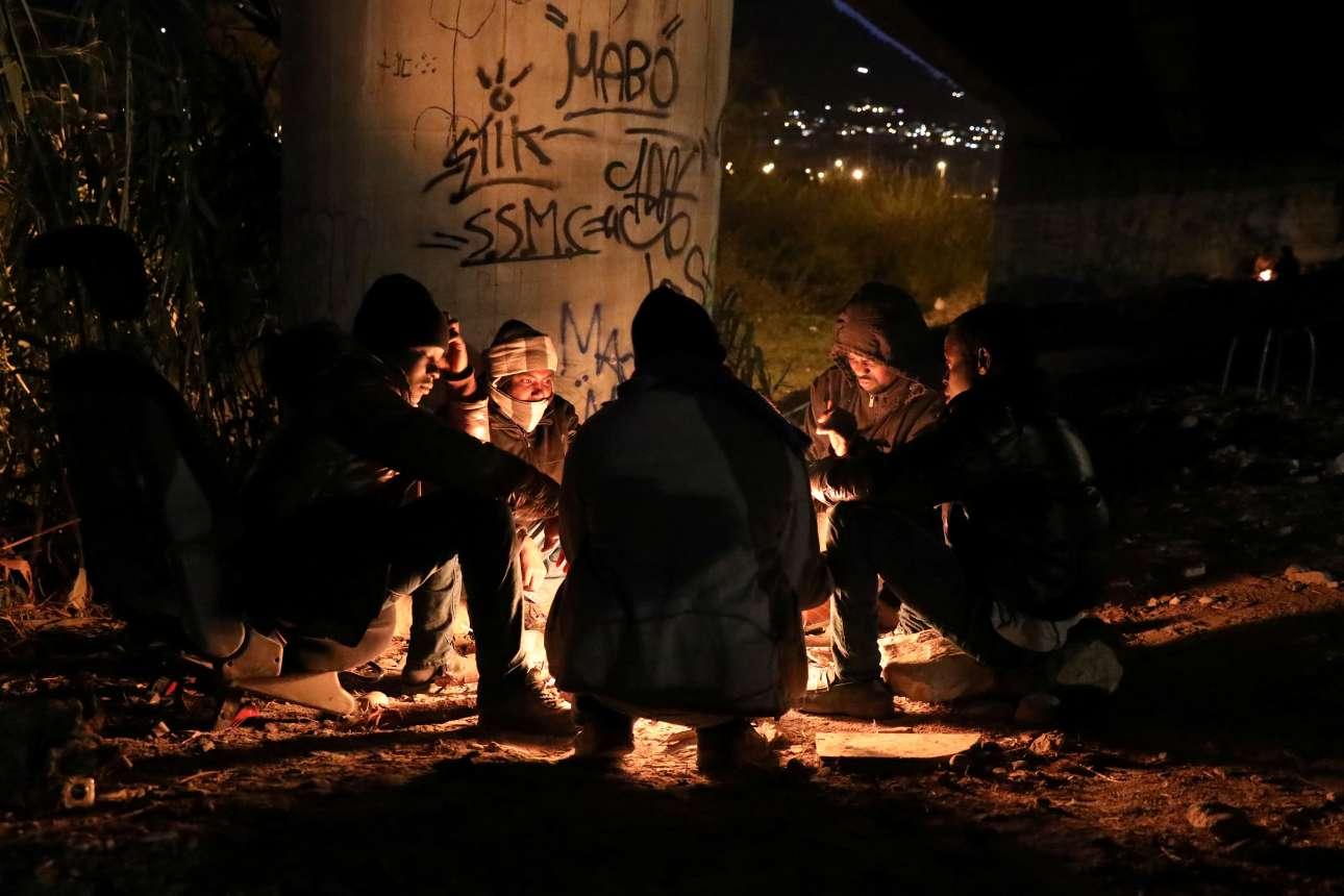 Εχει νυχτώσει και οι μετανάστες προσπαθούν να ζεσταθούν από μία μικρή που έχουν ανάψει κάτω από μια γέφυρα