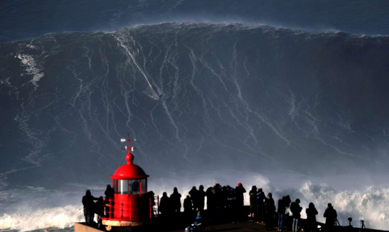 Παρασκευή, 19 Ιανουαρίου, Πορτογαλία. Κόσμος παρακολουθεί τον τολμηρό σέρφερ Σεμπάστιαν Στέουντερ ο οποίος δαμάζει ένα τεράστιο κύμα σε παραλία της πόλης Ναζαρέ
