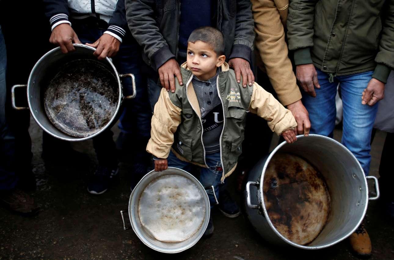 Τετάρτη, 24 Ιανουαρίου, Γάζα. Αγόρι από την Παλαιστίνη κρατά δύο μεγάλες κατσαρόλες κατά τη διάρκεια διαδήλωσης έξω από τα γραφεία των Ηνωμένων Εθνών