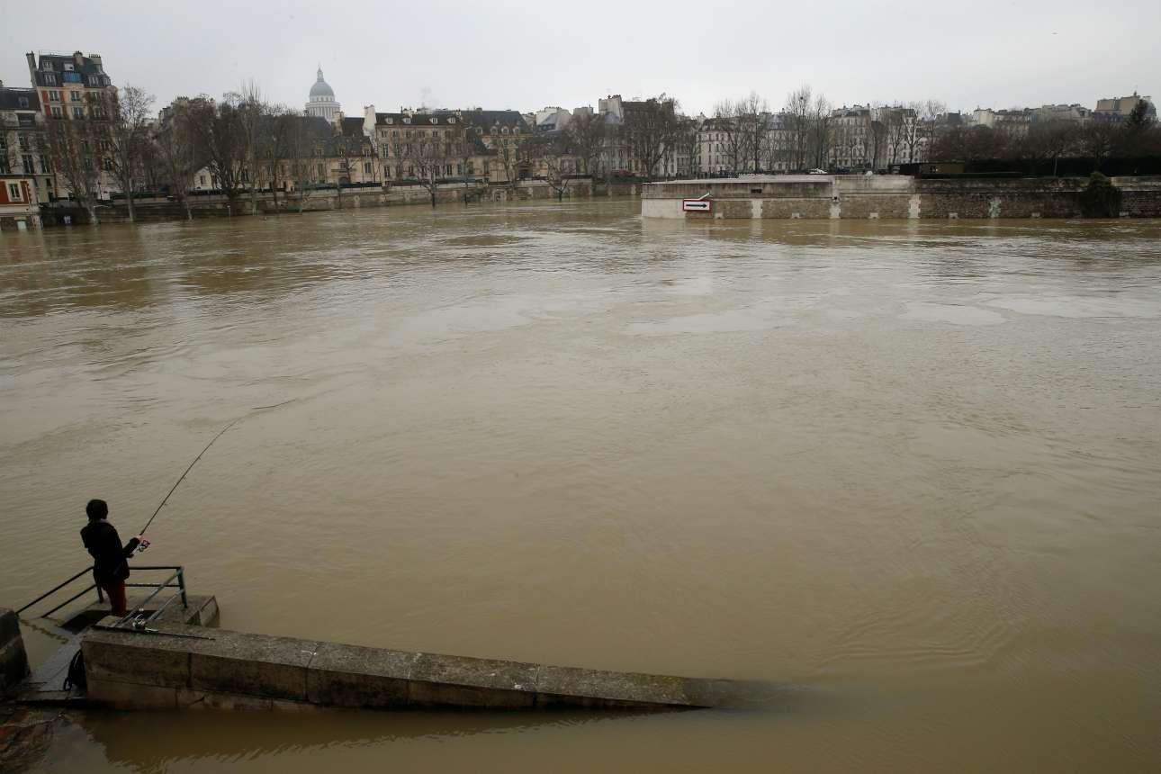 Γυναίκα ψαρεύει στα θολά νερά του ποταμού που διασχίζει την πρωτεύουσα της Γαλλίας