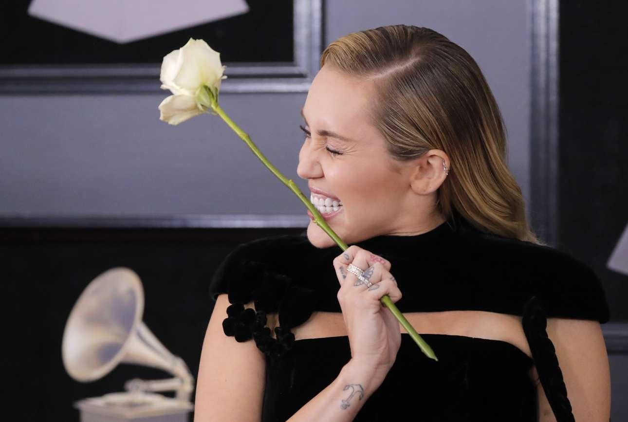 H Μάιλι Σάιρους δαγκώνει με νάζι ένα λευκό τριαντάφυλλο, το σύμβολο που επέλεξαν οι διοργανωτές για το κίνημα #MeToo κατά της σεξουαλικής παρενόχλησης