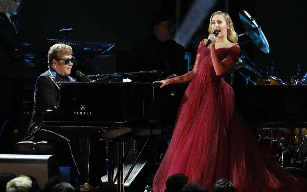 Ο σερ Ελτον Τζον στο πιάνο και η Μάιλι Σάιρους στο μικρόφωνο. Ερμηνεύουν το «Tiny Dancer»