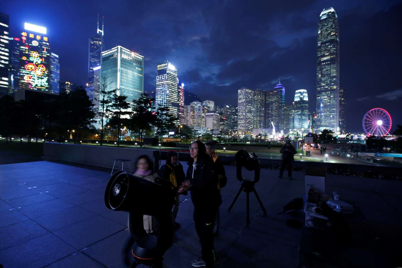 Τηλεσκόπια έτοιμα για δράση στο Χονγκ Κονγκ. Το εντυπωσιακό φαινόμενο είναι ορατό κυρίως από την κεντρική και ανατολική Ασία, την Ινδονησία και την Αυστραλία, που είχαν βράδυ στη διάρκεια της έκλειψης