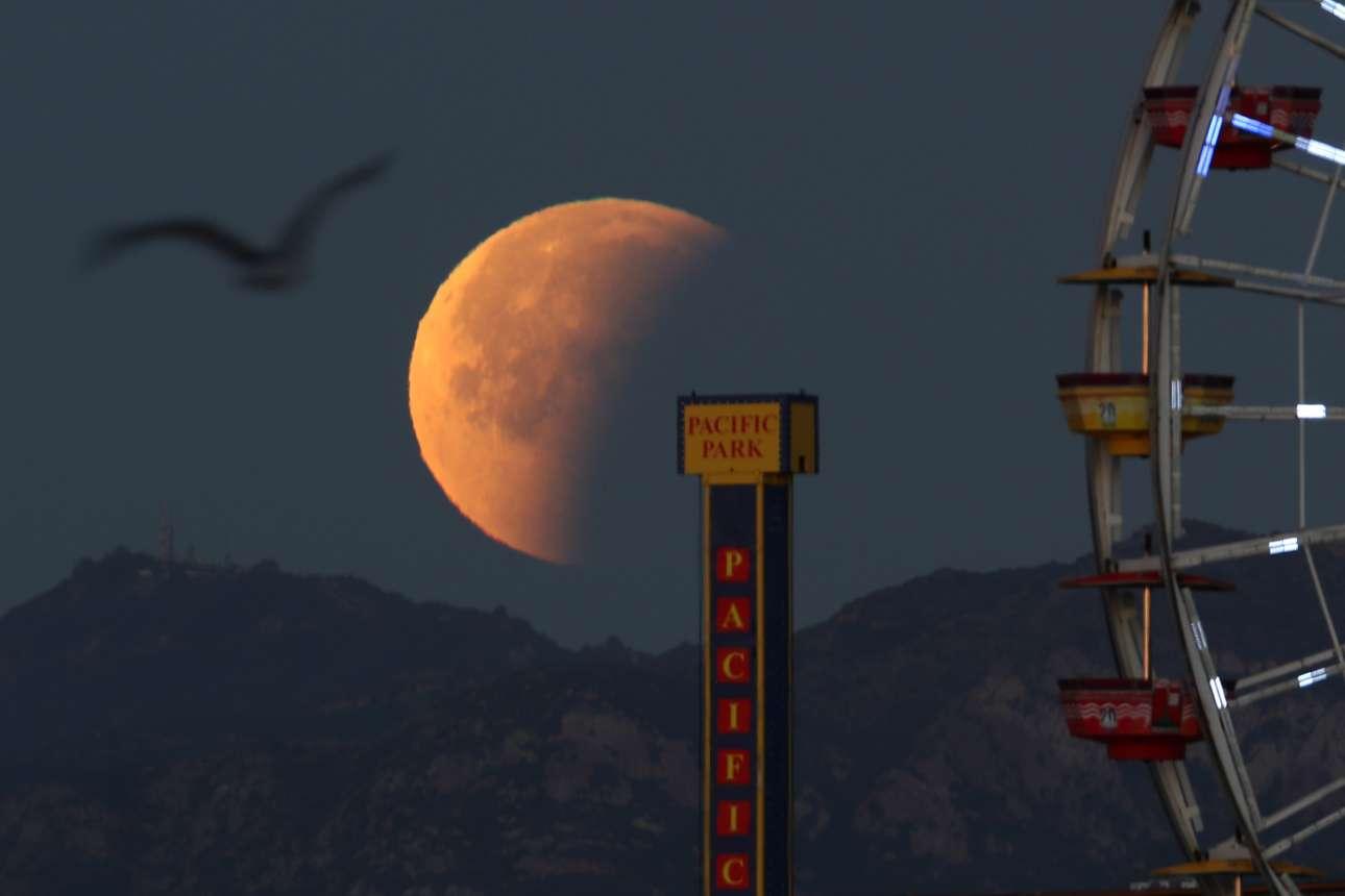 Η υπερ-Σελήνη ξεπροβάλει πίσω από τη ρόδα του λούνα παρκ της Σάντα Μόνικα στην Καλιφόρνια