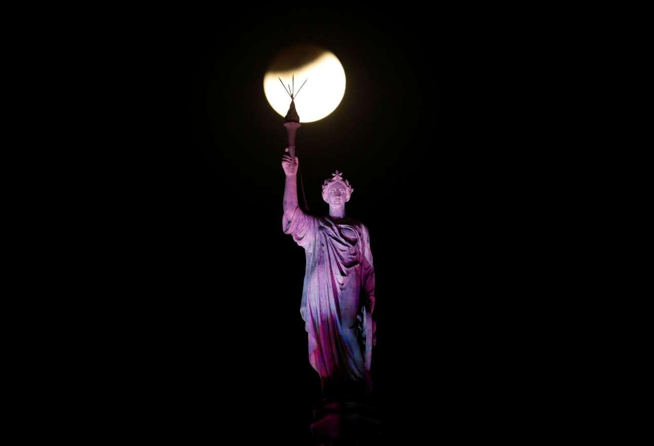 Η υπερ-Σελήνη σχεδόν στα χέρια του αγάλματος που κοσμεί τον σιδηροδρομικό σταθμό στην Μουμπάι της Ινδίας