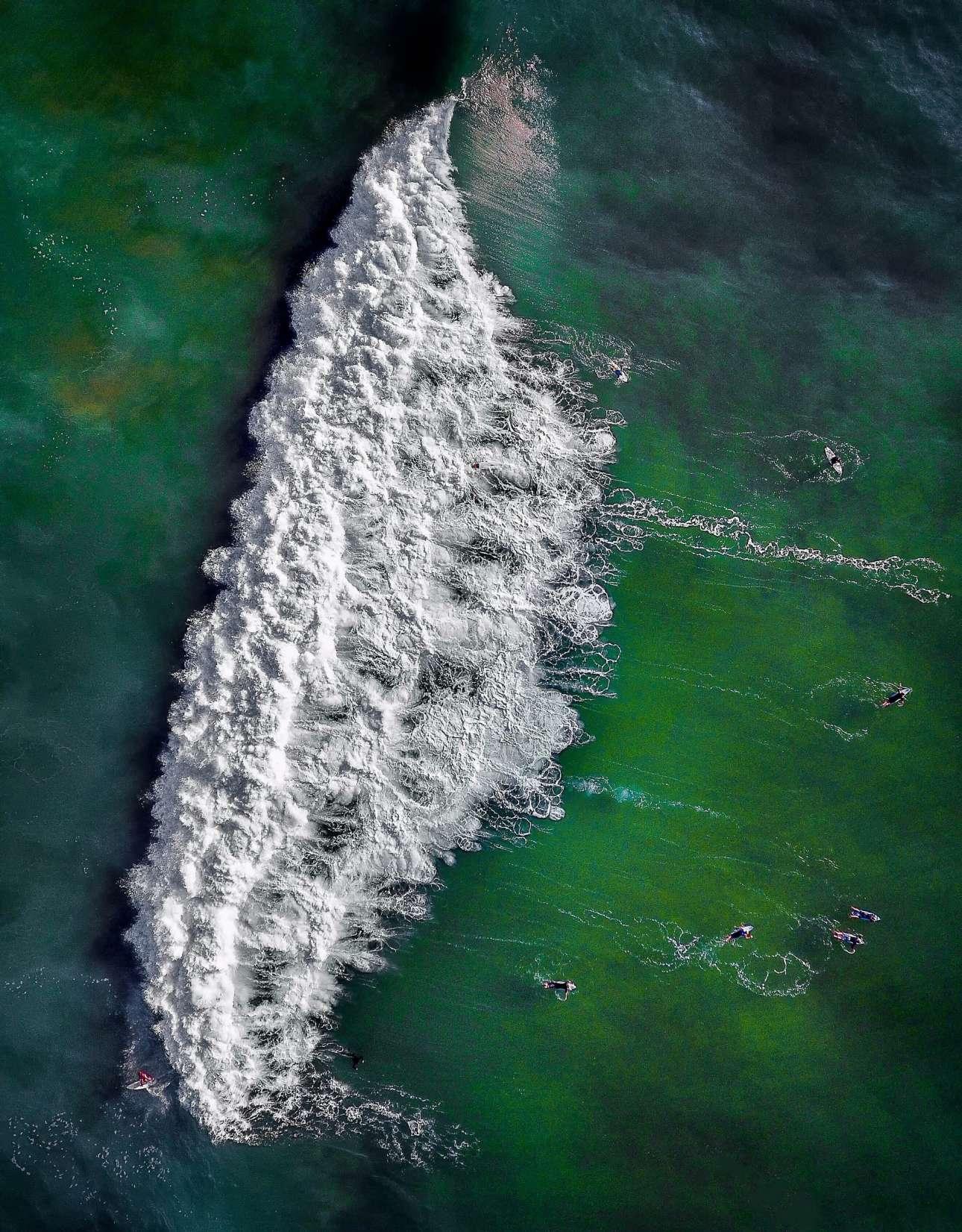 «Φωτογραφία της Χρονιάς». Σέρφερ περιμένουν στη σειρά για το τέλειο κύμα, σε μία παραλία του Σίδνεϊ
