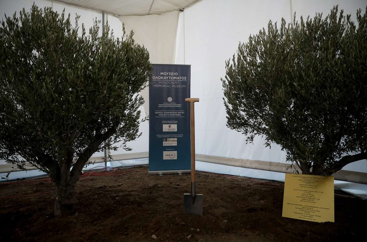 To φτυάρι και οι δύο ελιές περιμένουν τον Πρωθυπουργό και τον ισραηλινό πρόεδρο Ρίβλιν για τη συμβολική φύτευση: «Σήμερα θα φυτέψουμε τα πρώτα δέντρα, ελιές, για να ριζώσει η μνήμη στη συνείδηση των λαών μας» τόνισε ο κ. Τσίπρας