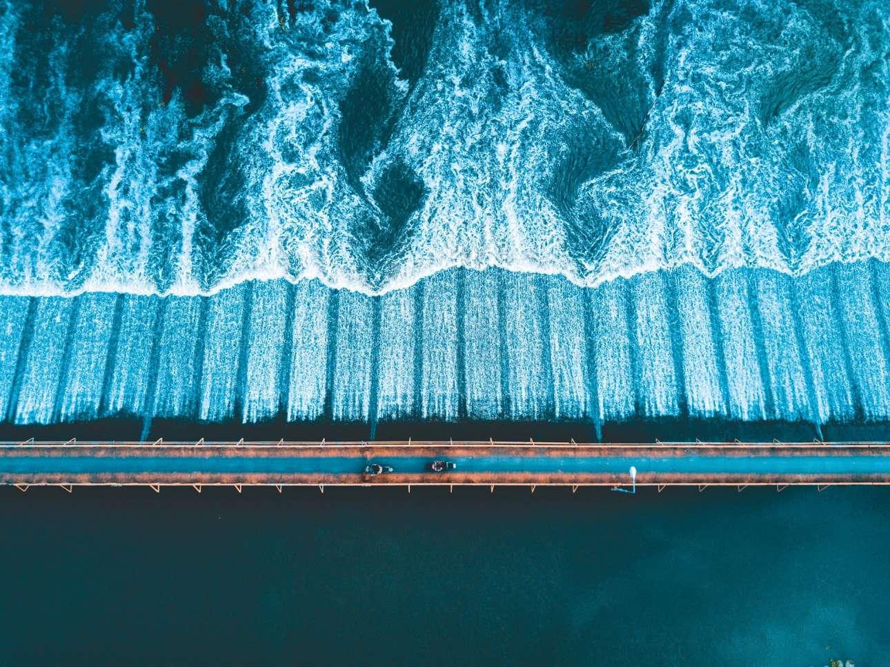 «Θέα από Ψηλά». Ηλιοβασίλεμα, ο ποταμός Πινγκ και δύο ντόπιοι που οδηγούν μηχανάκι πάνω στην ειδικά σχεδιασμένη γέφυρα. Οταν ο φωτογράφος συνάντησε αυτή την υπέροχη στιγμή στο Τσιάνγκ Μάι της Ταϊλάνδης, έσπευσε να την απαθανατίσει με το drone του