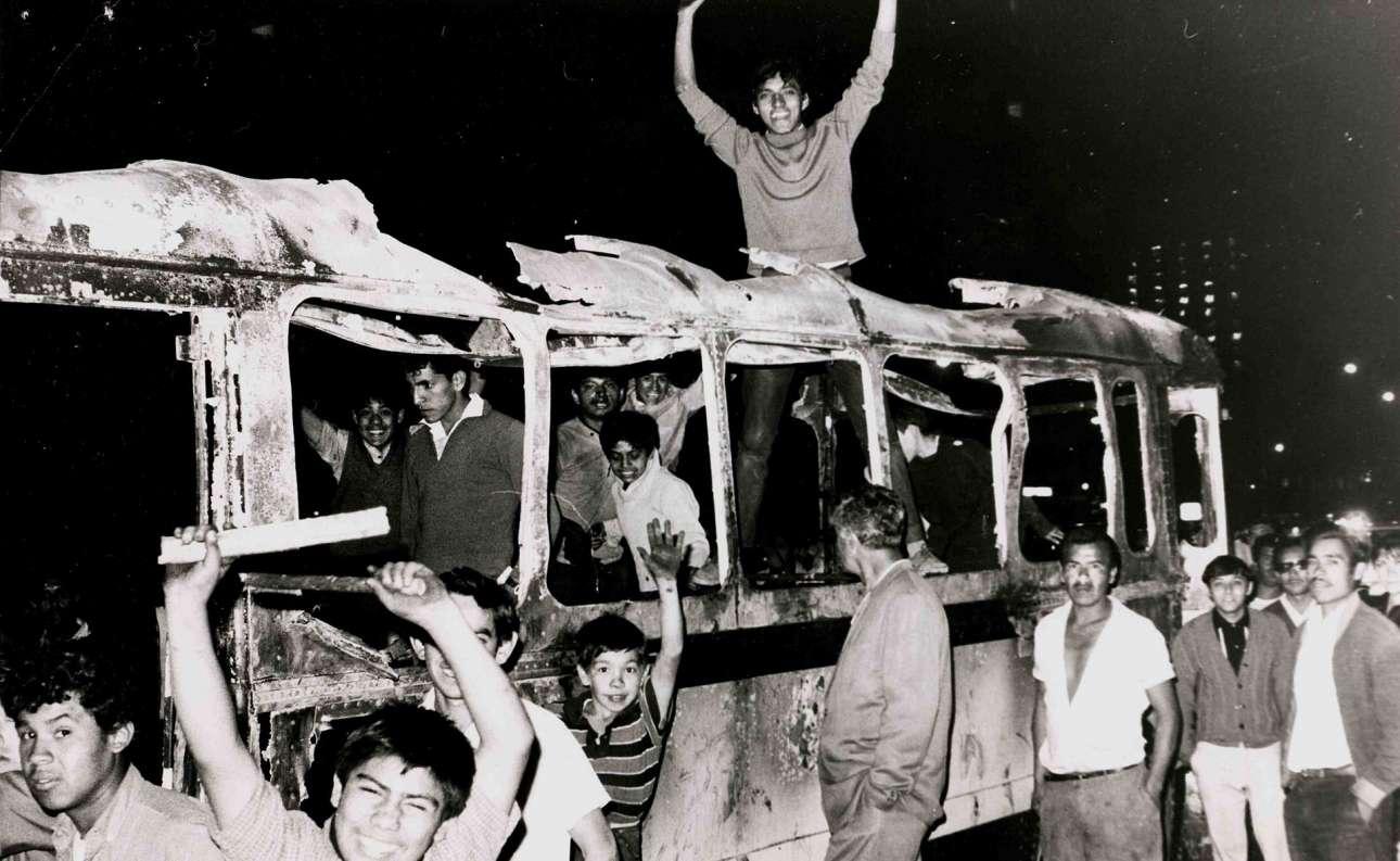 Μία ακόμη μαύρη σελίδα στην ιστορία του 1968, η σφαγή του Τλατελόλκο στο Μεξικό, όπου μία ειρηνική φοιτητική διαδήλωση μετατράπηκε σε μακελειό. Στις 2 Οκτωβρίου του 1968 και δέκα μέρες πριν από τους Ολυμπιακούς Αγώνες του Μεξικού, αστυνομικοί δολοφονούν 350 φοιτητές και πολίτες με πρόσχημα την ασφάλεια των αγώνων... Στη φωτογραφία μεξικανοί φοιτητές σε ένα καμένο λεωφορείο διαδηλώνουν και ζητούν την απομάκρυνση του στρατού από τους χώρους του πανεπιστημίου