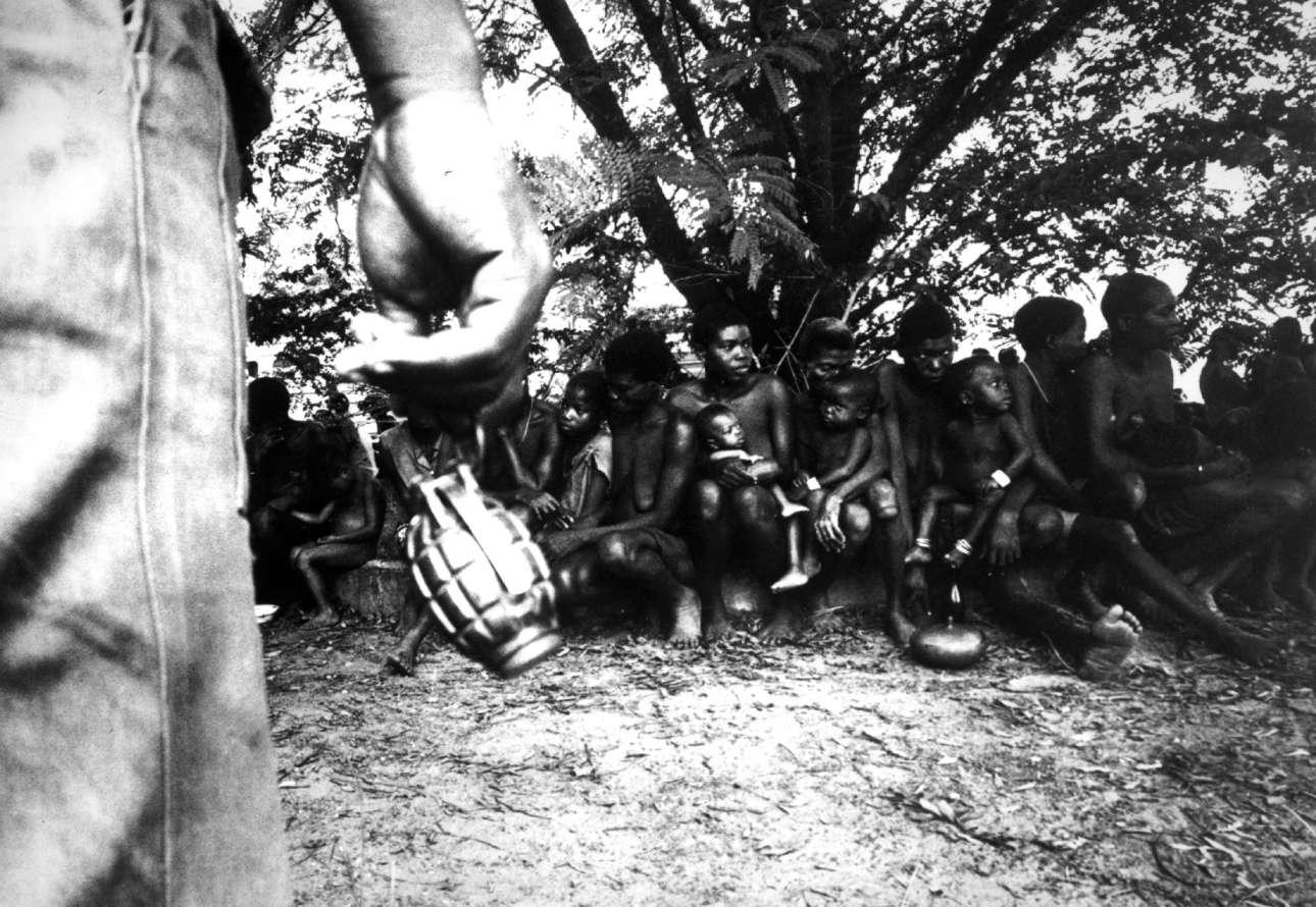 Ιούλιος, 1968. Ομοσπονδιακός στρατιώτης με χειροβομβίδα στα χέρια φρουρεί αιχμάλωτες γυναίκες και παιδιά της φυλής των Ιμπο, κατά τη διάρκεια του εμφυλίου πολέμου στη Νιγηρία, γνωστού και ως «Πόλεμος της Μπιάφρα»