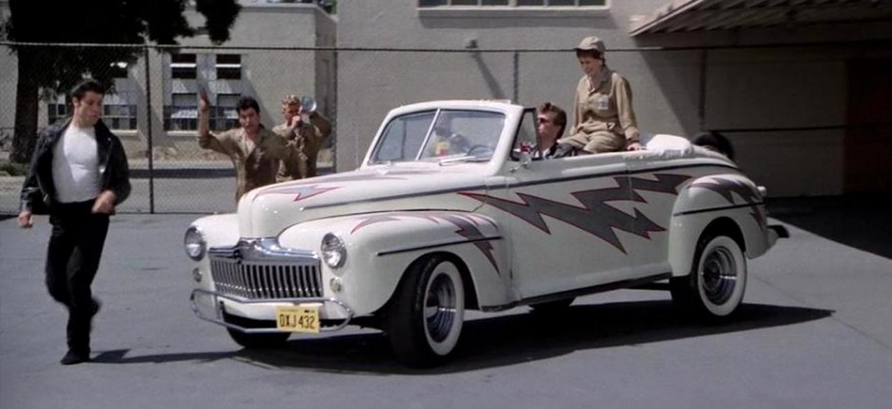 Ford Deluxe. Εντυπωσιακό, λευκό, ροκ εντ ρολ, μπέιμπι. Θα μας θυμίζει για πάντα τον ρόλο του Τραβόλτα στο «Grease», την εμβληματική αμερικανική μουσική και αισθηματική κωμική ταινία του 1978, σε σκηνοθεσία Ράνταλ Κλάιζερ