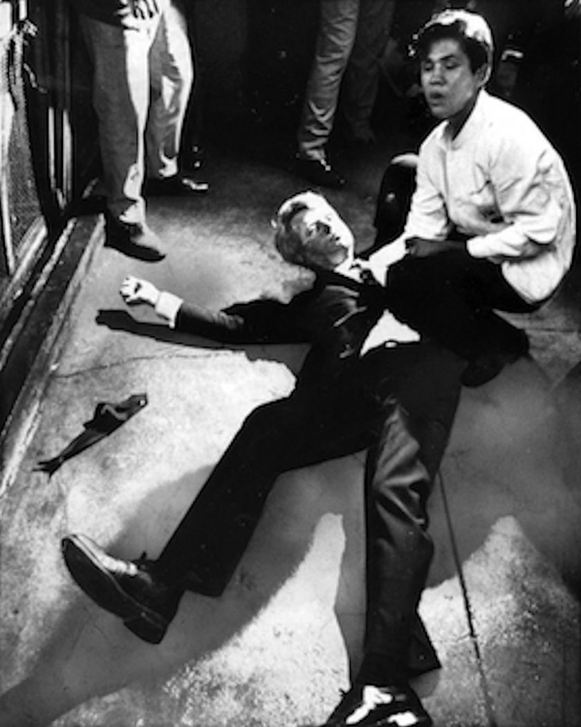 Ο γερουσιαστής Ρόμπερτ Κένεντι κείτεται ημιθανής, έχοντας πυροβοληθεί στο κεφάλι και τον λαιμό. Δίπλα του ο σερβιτόρος του ξενοδοχείου Ambassador Χουάν Ρομέρο προσπαθεί να τον καθησυχάσει. Ο παλαιστίνιος μετανάστης Σιρχάν Σιρχάν δολοφόνησε τον Κένεντι στις 5 Ιουνίου του 1968, εξαγριωμένος για τις φιλοϊσραηλινές απόψεις του γερουσιαστή