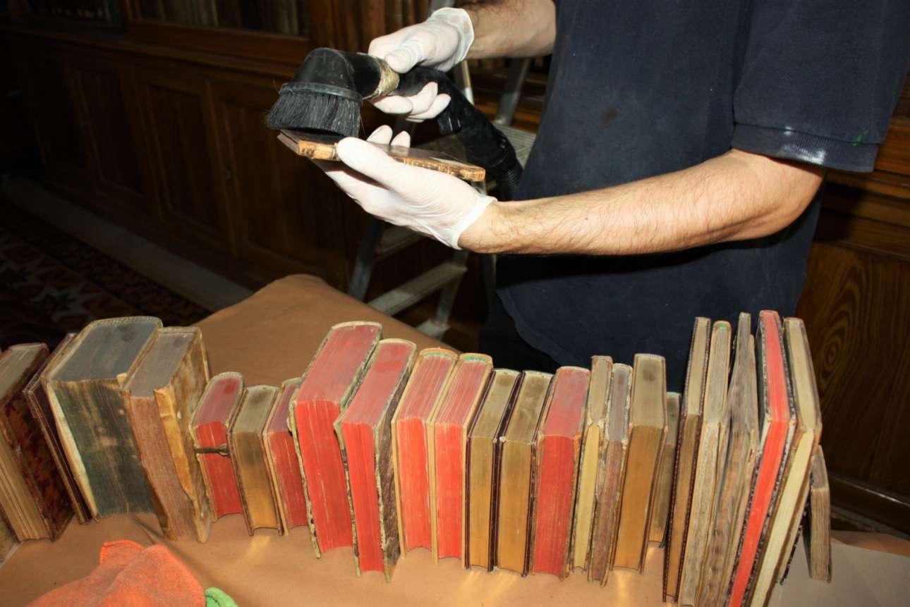 Τα βιβλία καθαρίζονται ένα - ένα από την σκόνη που είχε συσσωρευτεί τόσα χρόνια στα ράφια της Εθνικής Βιβλιοθήκης