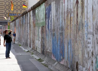 A tourist eyes the graffiti and paintings on Tuesday, 12 August 2003 at the remaining part of what once used the be the Berlin Wall, in the Berlin suburb of Friedrichshain. Germany marks the 42nd anniversary of the building of the wall on Wednesday, 13 August. East German border troops began with the construction of the wall 13 August 1961 and cut off the eastern parts of Berlin from the rest of the city. The construction of the wall through all of Germany took place simultaneously. EPA PHOTO/DPA/WOLFGANG KUMM