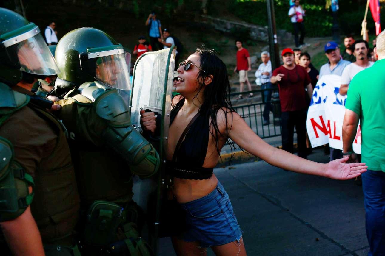 Τρίτη, 30 Ιανουαρίου, Χιλή. Η διαδηλώτρια και οι άνδρες της αστυνομίας. Στιγμιότυπο από πορεία διαμαρτυρίας στο Σαντιάγο, υπέρ της εθνικοποίησης των αποθεμάτων λιθίου στη χώρα