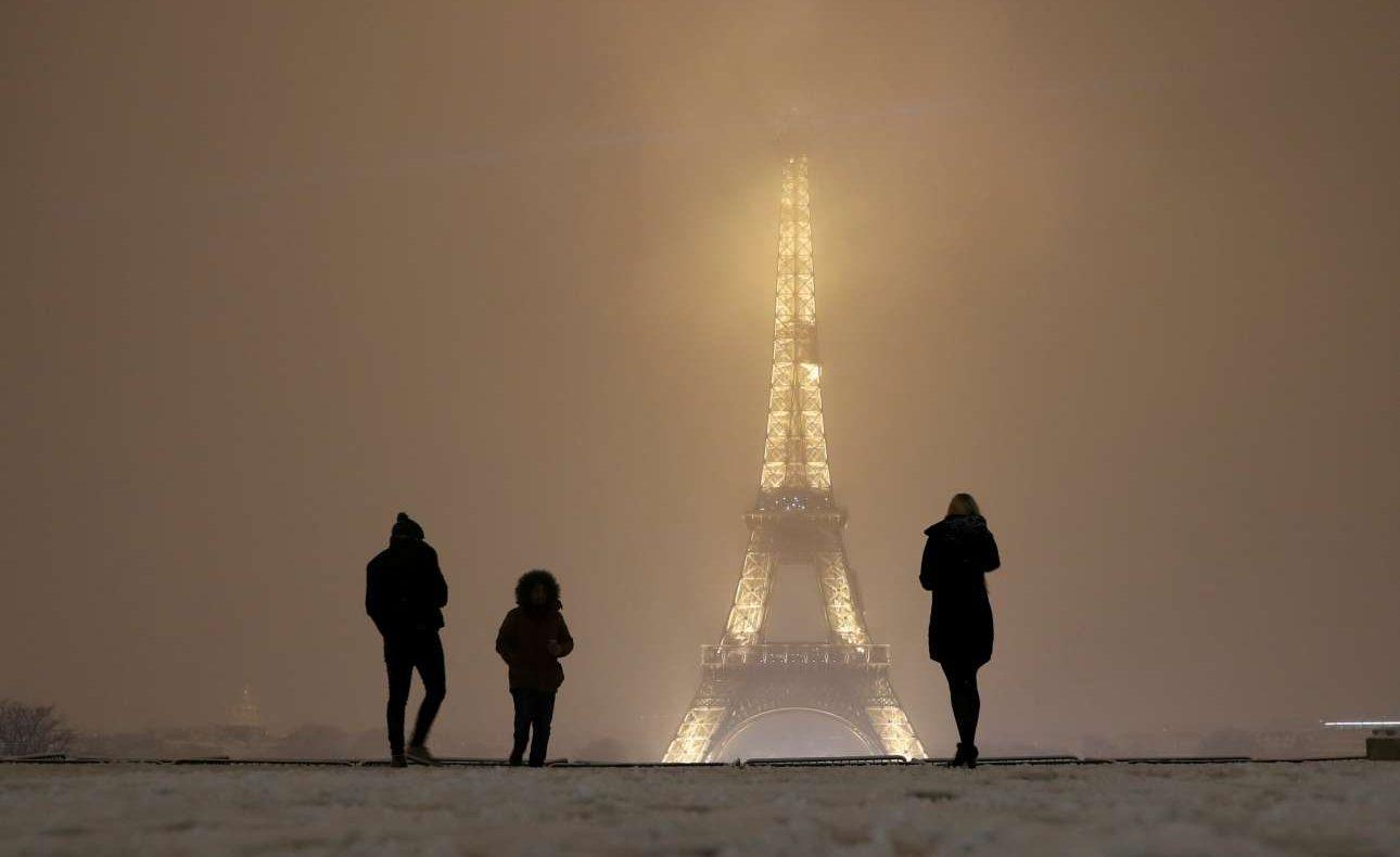 Τουρίστες θαυμάζουν τον φωταγωγημένο Πύργο του Αϊφελ εν μέσω χιονοθύελλας. Η θερμοκρασία τη νύχτα της Τετάρτης προς Πέμπτη μπορεί να πέσει κάτω από τους 10 βαθμούς υπό το μηδέν