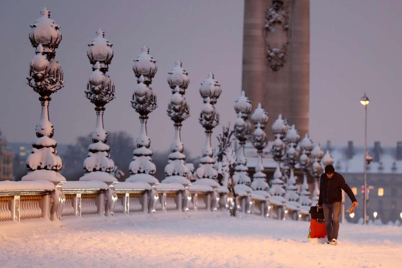 Σέρνοντας μία κόκκινη βαλίτσα στην χιονισμένη γέφυρα του Αλέξανδρου Γ'