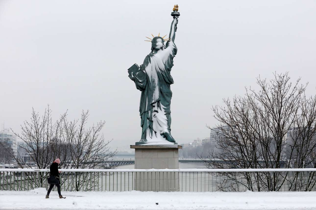 Μια περαστική προσπερνά βιαστικά το χιονισμένο αντίγραφο του Αγάλματος της Ελευθερίας στη γέφυρα της Γρενέλ. Ως γνωστόν το αυθεντικό Αγαλμα της Ελευθερίας στη Νέα Υόρκη ήταν δώρο της Γαλλίας προς τον αμερικανικό λαό