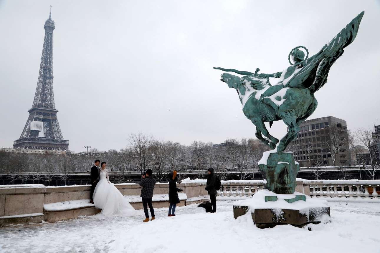 Η βιομηχανία των γάμων δεν σταματά. Ενα ζευγάρι νιόπαντρων Κινέζων φωτογραφίζονται στο χιόνι με φόντο -τι άλλο;- τον Πύργο του Αϊφελ