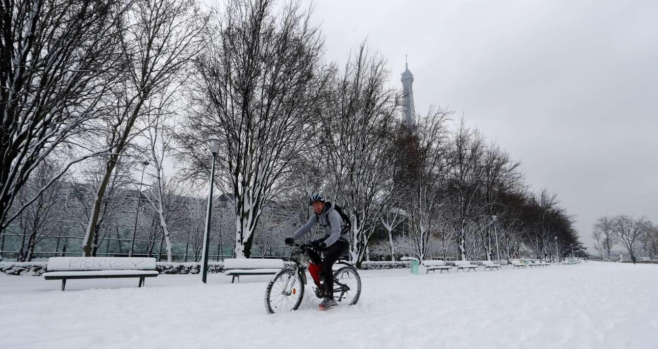 Ποδηλάτης πασχίζει να διασχίσει έναν χιονισμένο δρόμο κάτω από τον Πύργο του Αϊφελ