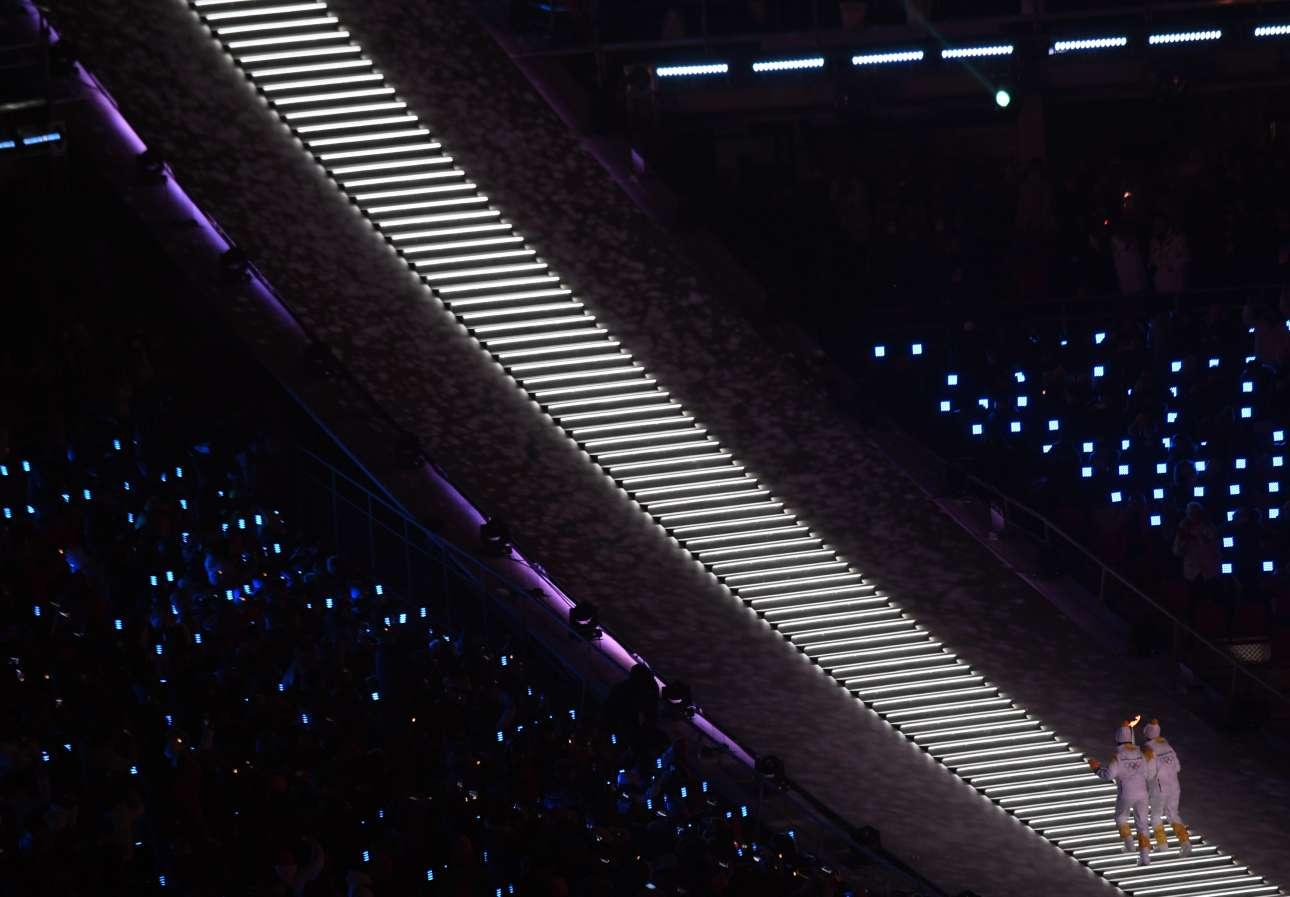 Ο συμβολισμός: ένας Βορειοκορεάτης και ένας Νοτιοκορεάτης ανεβαίνουν μαζί τα σκαλιά για ανάψουν την ολυμπιακή φλόγα