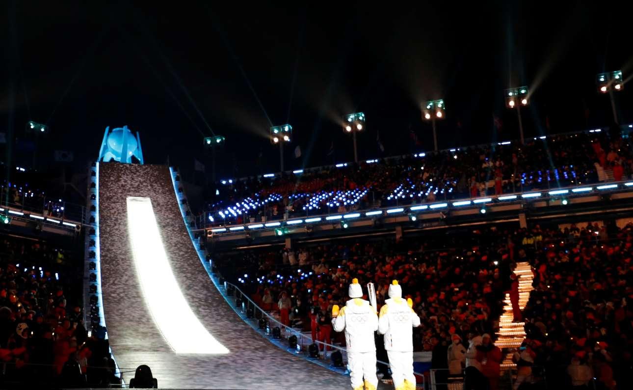 Η κορύφωση της τελετής έναρξης. Δύο παίκτες του χόκεϊ επί πάγου της κοινής κορεατικής ομάδας έτοιμοι για να ανάψουν τον βωμό