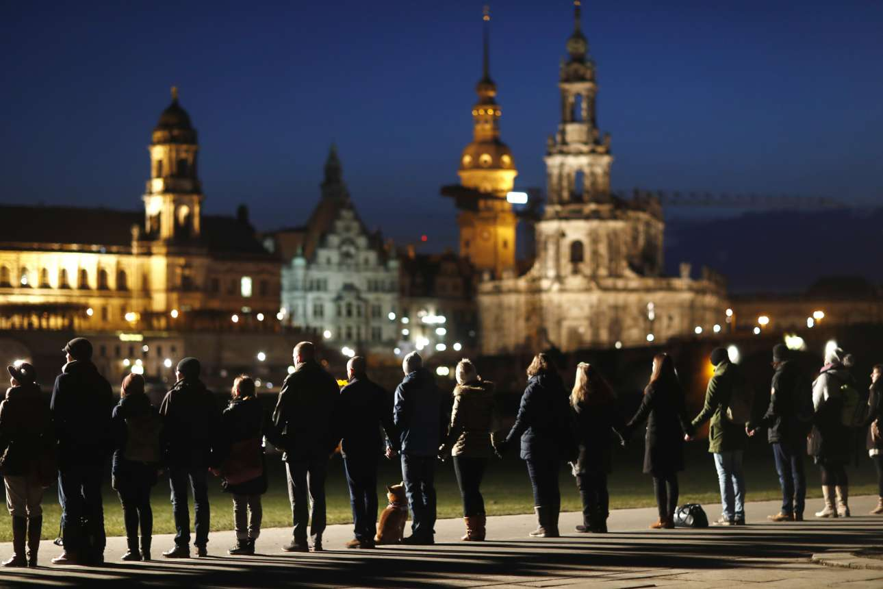 Τετάρτη, 14 Φεβρουαρίου, Γερμανία. Πλήθος κόσμου σχηματίζει ανθρώπινη αλυσίδα έξω από τον καθεδρικό ναό της Παναγίας (Frauenkirche) στη Δρέσδη στο πλαίσιο των εκδηλώσεων μνήμης για το βομβαρδισμό της πόλης κατά τη διάρκεια του Β' Παγκοσμίου Πολέμου