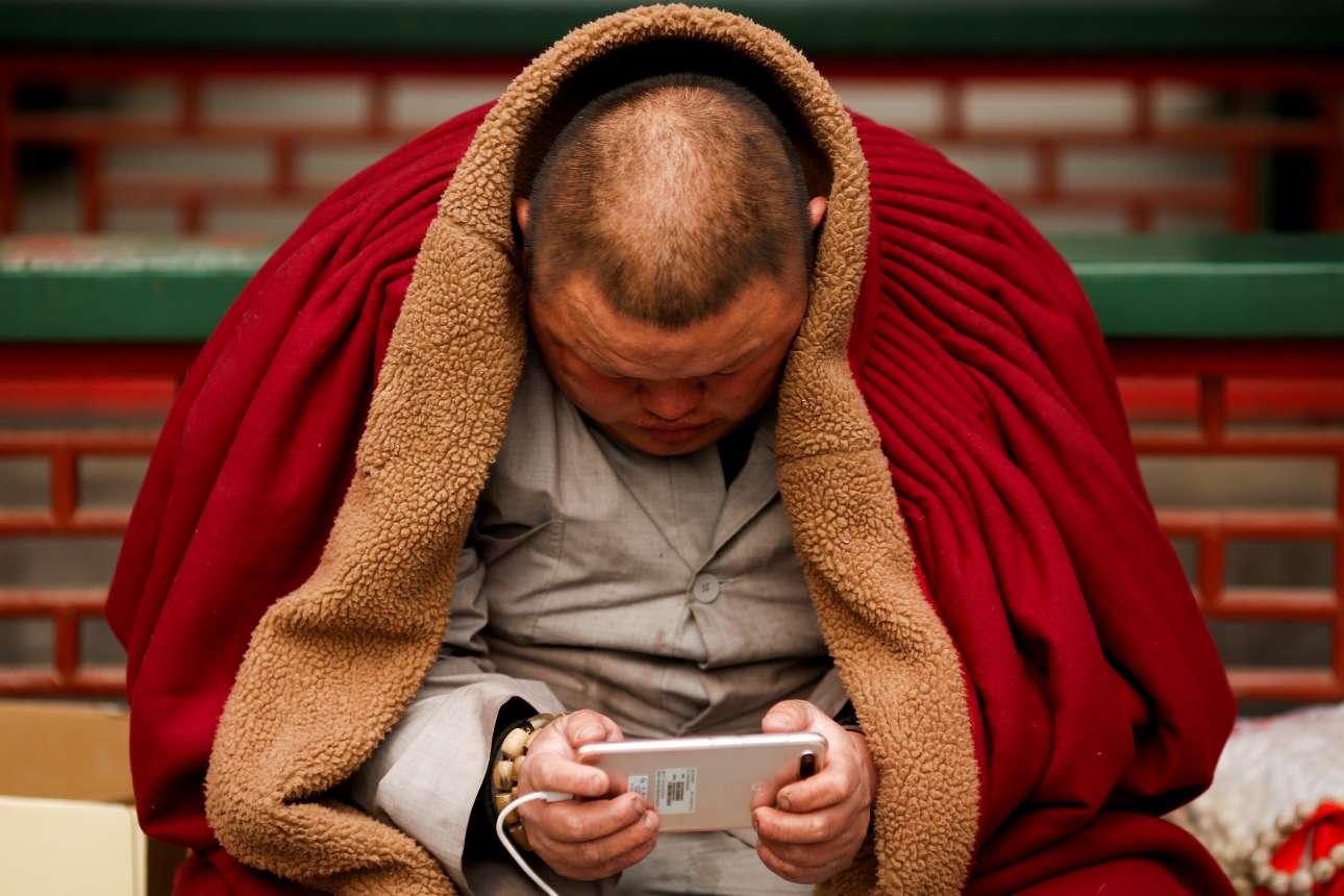 Σάββατο, 17 Φεβρουαρίου, Κίνα. Βουδιστής χαλαρώνει βλέποντας κάτι στο κινητό του ενώ βρίσκεται στο εσωτερικό ενός ναού στο Πεκίνο. Η Κίνα υποδέχτηκε τις πρώτες πρωινές ώρες της Παρασκευής (τοπική ώρα) τη χρονιά του Σκύλου