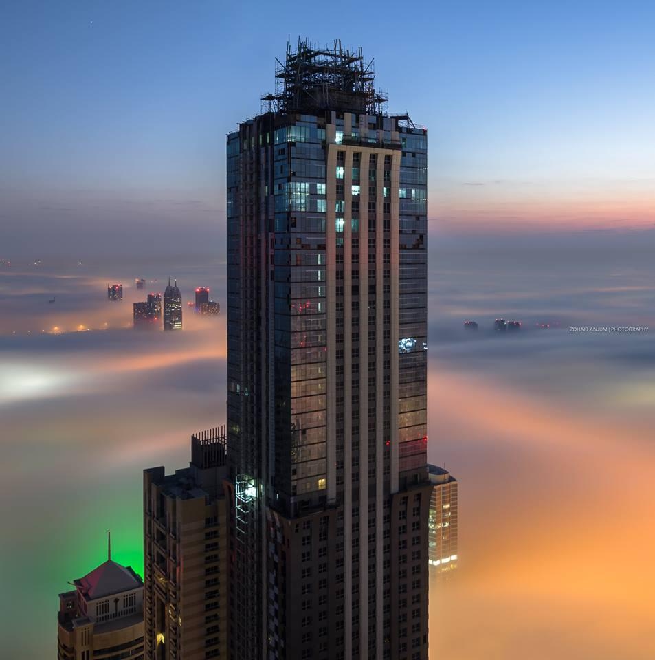 Τα φώτα των κτιρίων μπλέκονται με την ομίχλη δημιουργώντας ένα ονειρικό τοπίο