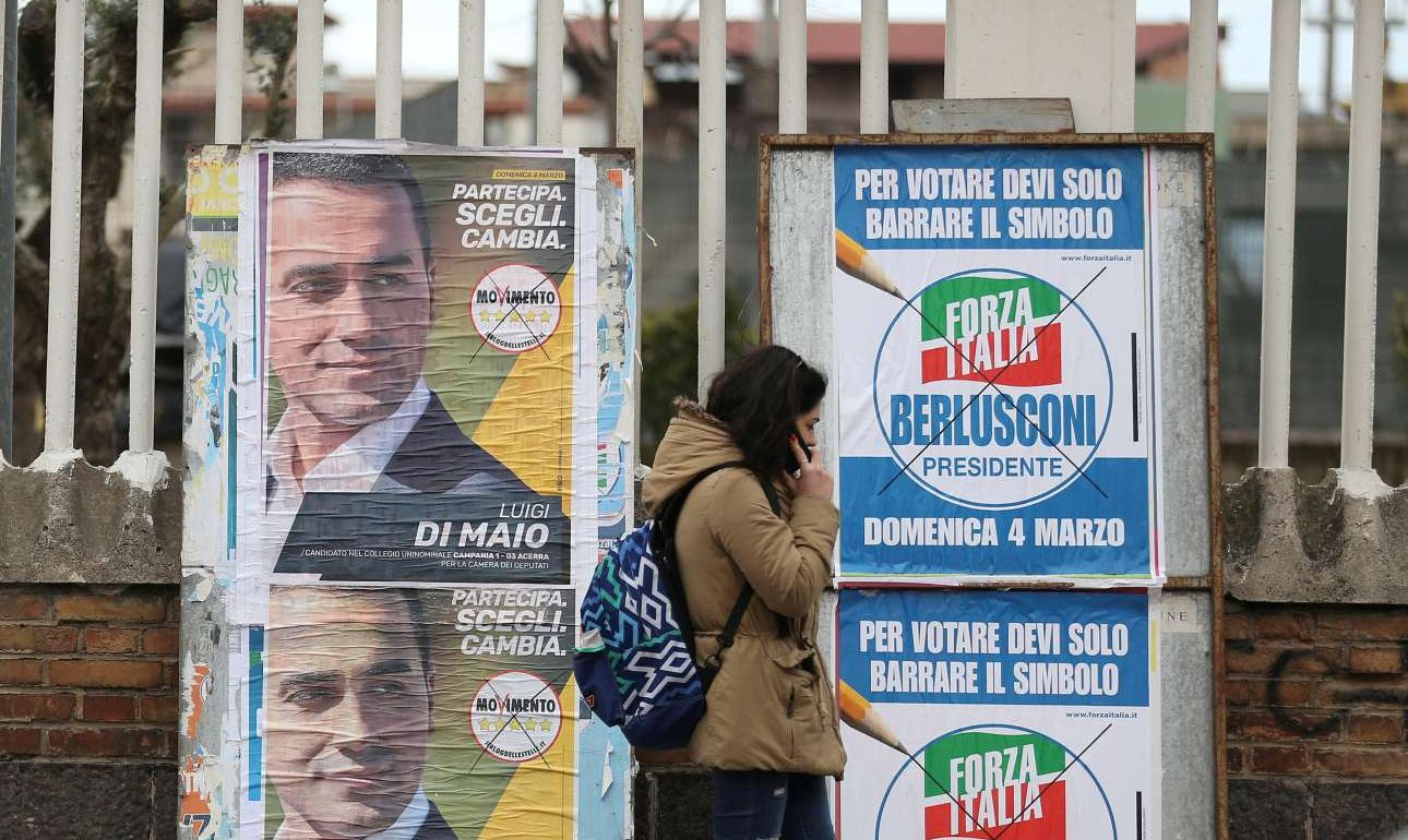 Μία κοπέλα μιλάει στο τηλέφωνο μπροστά από τις προεκλογικές αφίσες των δύο πρωταγωνιστών. Του Κινήματος 5 αστέρων με επικεφαλής τον Ντι Μάιο και του Forza Italia,το κόμμα του «Καβαλιέρε» (REUTERS/ Alessandro Bianchi/ File Photo)