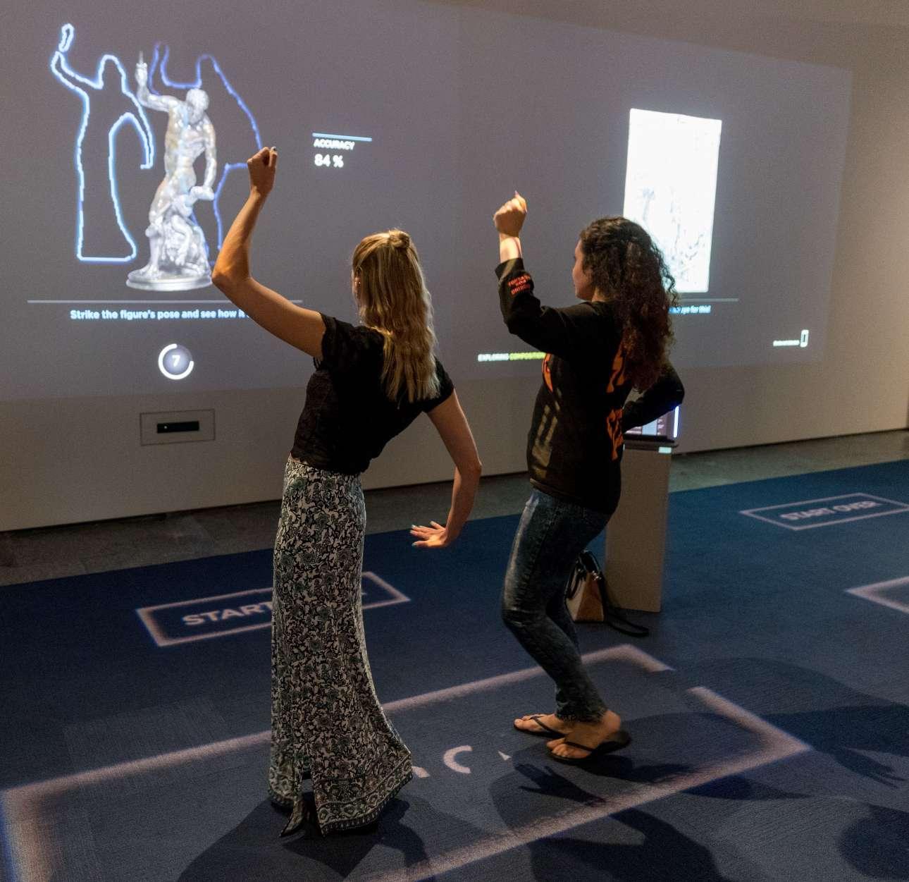 Επισκέπτες του Μουσείου Τέχνης του Κλίβελαντ αλληλεπιδρούν με κάποιο από τα εκθέματα που εμφανίζονται μπροστά τους σε ψηφιακή μορφή.