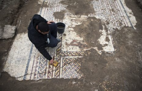 epa06505192 An Israel Antiquities Authority employee works a mosaic from the Roman period at an archeological excavation site in the Caesarea National Park, Israeli, 08 February 2018. According to the directors of the excavation for the Israel Antiquities Authority: 'This colorful mosaic, from the 2nd–3rd centuries CE, measuring more than 3.5 x 8 meters, is of a rare high quality. It features three figures, multicolored geometric patterns and a long inscription in Greek, which were damaged by the Byzantine building constructed on'. The mosaic was excavated during the reconstruction work on the Crusaders-era.  EPA/ATEF SAFADI