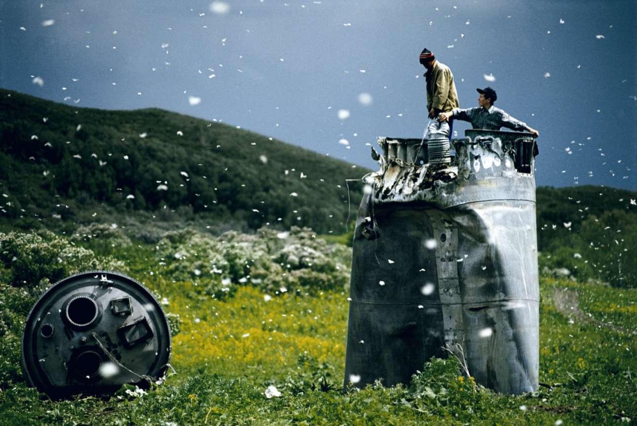 Ανάμεσα σε χιλιάδες λευκές πεταλούδες, κάτοικοι της περιοχής Αλτάι στη Ρωσία μαζεύουν παλιοσίδερα από ένα συνθλιμμένο διαστημόπλοιο, το 2000. Οι περιβαλλοντολόγοι ανησυχούν για το μέλλον της περιοχής εξαιτίας των τοξικών αποβλήτων από τα καύσιμα πυραύλων