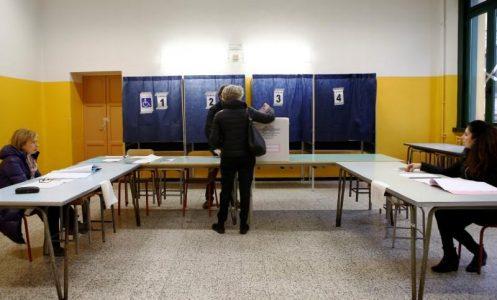 Una donna vota in un seggio elettorale a Milano. REUTERS/Alessandro Garofalo