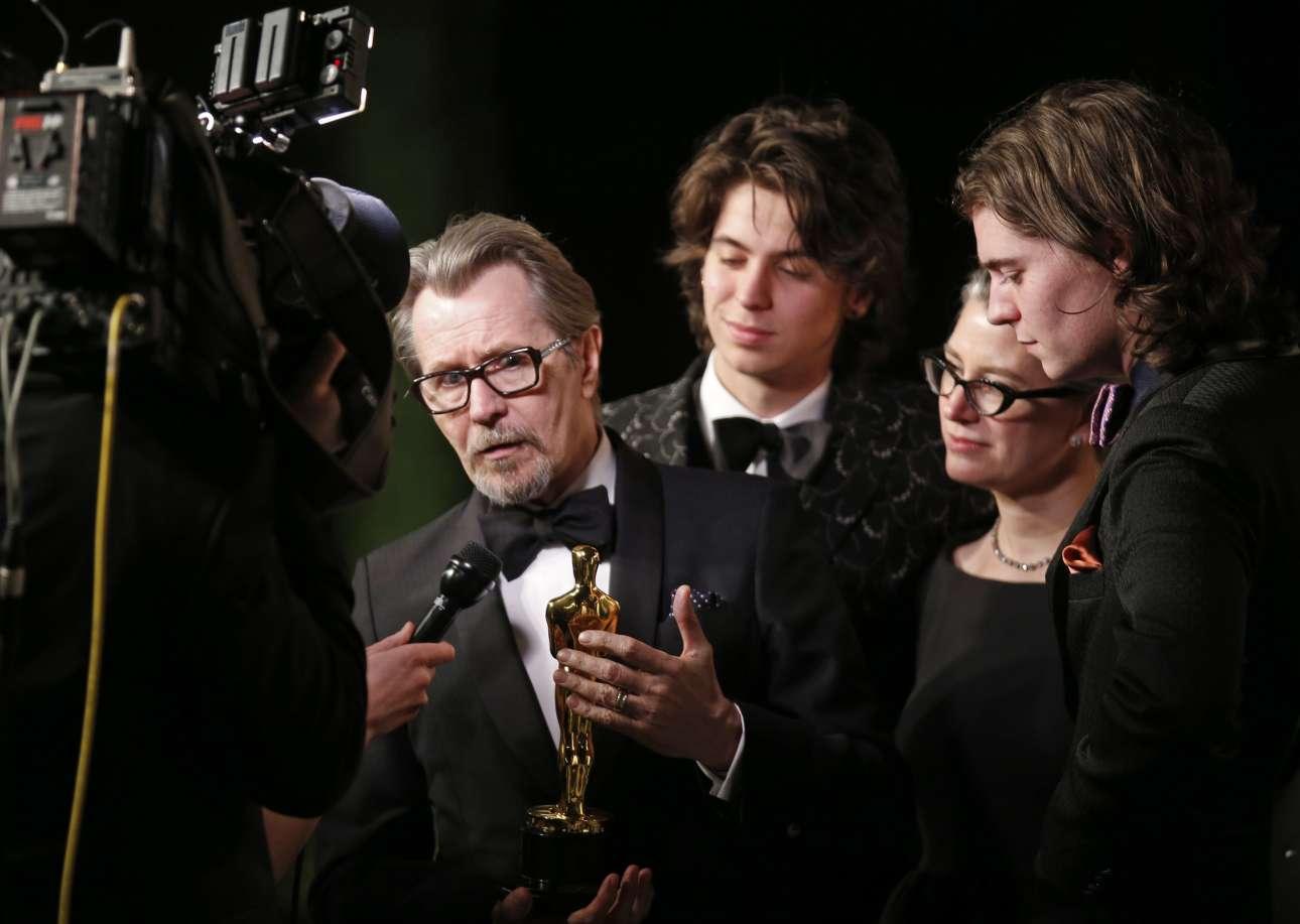 O Γκάρι Ολντμαν μιλά στα τηλεοπτικά συνεργεία πλαισιωμένος από την οικογένειά του, τη σύζυγό του Γκιζέλ Σμιτ και τους γιους του, Γκιούλιβερ (δεύτερος αριστερά) και Τσάρλι