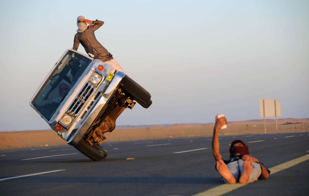 Δευτέρα, 12 Μαρτίου, Σαουδική Αραβία. Ανδρας βγάζει σέλφι τη στιγμή που πίσω του επιχειρείται ένα ακροβατικό με αυτοκίνητο στην πόλη Ταμπούκ