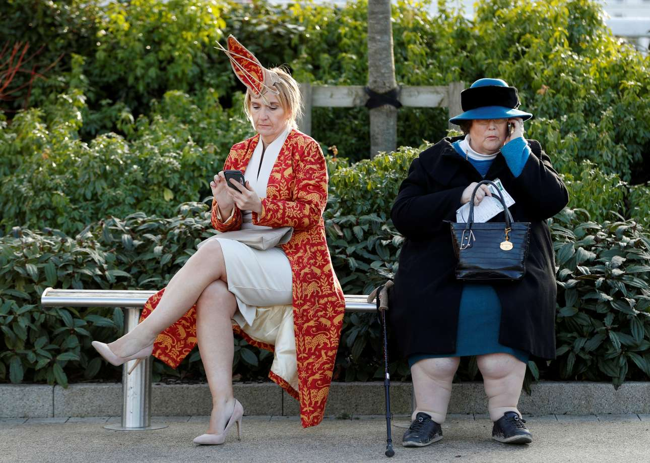Τετάρτη, 14 Μαρτίου, Βρετανία. Θεατές του ιπποδρομιακού φεστιβάλ του Τσέλτεναμ με «κλασικό» αγγλικό ντύσιμο περιμένουν την έναρξη των αγώνων