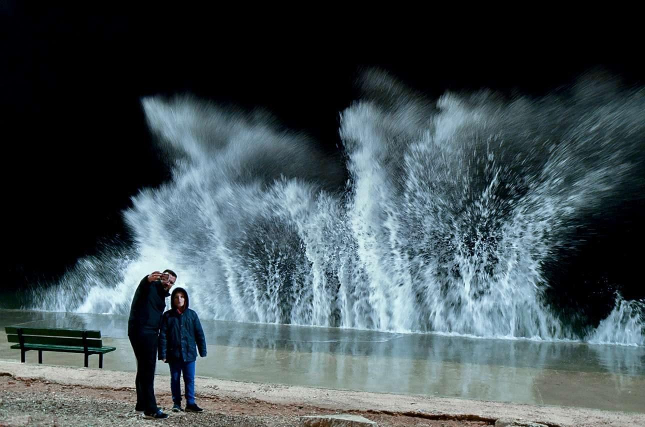 Τρίτη, 13 Μαρτίου, Αττική. Στιγμιότυπο από τη μαρίνα Αλίμου, στην Αθήνα, με έναν πατέρα να φωτογραφίζεται με τον γιο του με φόντο τα κύματα που σκάνε στην ακτή