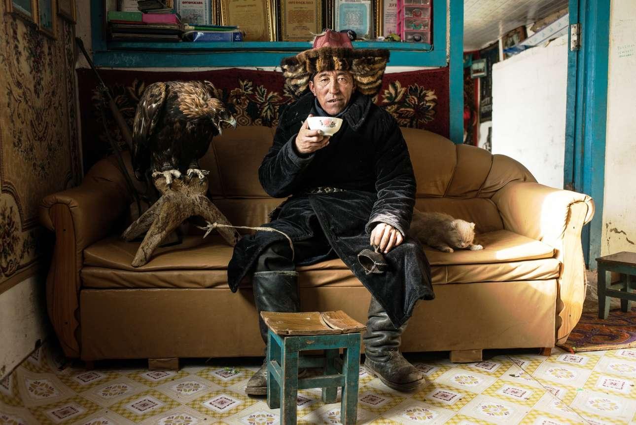 Βραβείο κατηγορία Ανθρωποι. Ενα πορτρέτο που προσφέρει μία μοναδική ματιά στον κόσμο του μογγόλου κυνηγού. Ο άνδρας της φωτογραφίας κάθεται και πίνει τσάι ανάμεσα στη γάτα του και τον θηλυκό χρυσό αετό, τον οποίο τον χρησιμοποιεί για να κυνηγάει αλεπούδες και περιστασιακά λύκους. Σύμφωνα με τον φωτογράφο, οι κυνηγοί στη Δυτική Μογγολία αντιμετωπίζουν το μεγαλοπρεπές αυτό αρπακτικό πουλί σαν μέλος της οικογένειάς τους