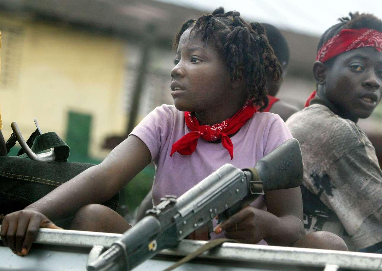 Νεαρό κορίτσι στρατιώτης επιβιβάζεται σε ένα αυτοκίνητο ανταρτών που είναι έτοιμο να επιτεθεί έξω από την πρωτεύουσα της Λιβερίας, Μονρόβια, στις 19 Ιουλίου του 2003