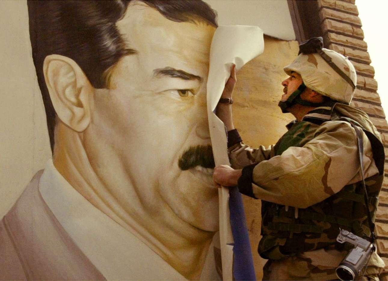 Αμερικανός στρατιώτης ξεκολλά ένα πόστερ του Σαντάμ Χουσεΐν στην πόλη Σαφκάν του Ιράκ στις 21 Μαρτίου του 2003. Το χάος κυριαρχούσε στο νότιο Ιράκ καθώς οι συμμαχικές δυνάμεις συνέχιζαν τις προσπάθειές τους να ανατρέψουν τον ιρακινό πρόεδρο