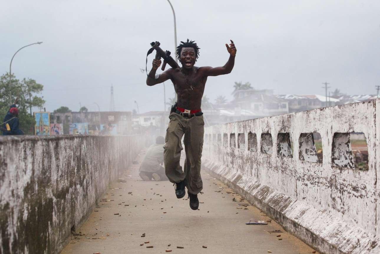 Ο Τζόζεφ Ντούο, διοικητής δυνάμεων του κυβερνητικού στρατού της Λιβερίας, πανηγυρίζει αφού έχει εκτοξεύσει μία ρουκέτα προς τις δυνάμεις των ανταρτών, τον Ιούλιο του 2003 στην πρωτεύουσα της χώρας, Μονρόβια. Η συγκεκριμένη φωτογραφία έμελλε να γίνει μία από τις πλέον διάσημες φωτογραφίες του Ελληνοαμερικάνου και από τις πιο εμβληματικές για τον εμφύλιο πόλεμο της Λιβερίας. Ο Χόντρος αργότερα επέστρεψε στην χώρα της Αφρικής και συναντήθηκε με τον Τζόζεφ. Μάλιστα, του έδωσε τα χρήματα για να επιστρέψει στο σχολείο και να ολοκληρώσει την εκπαίδευσή του